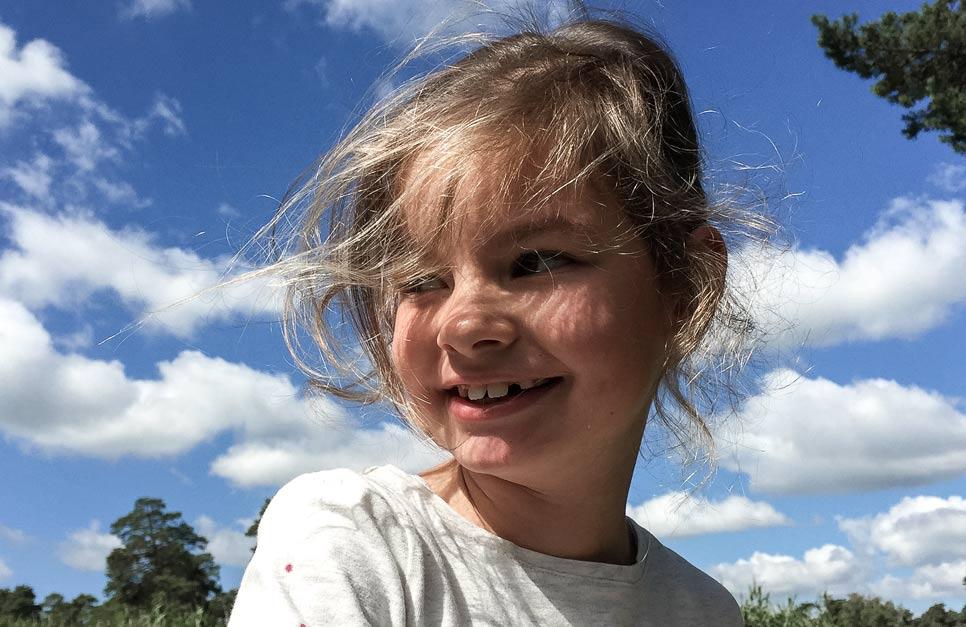 Lachendes Kind vor blauem Himmel