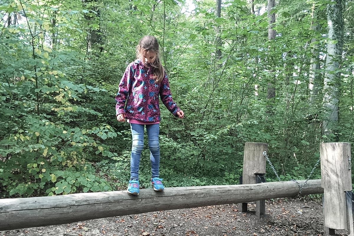 Kind balanciert auf Baumstamm