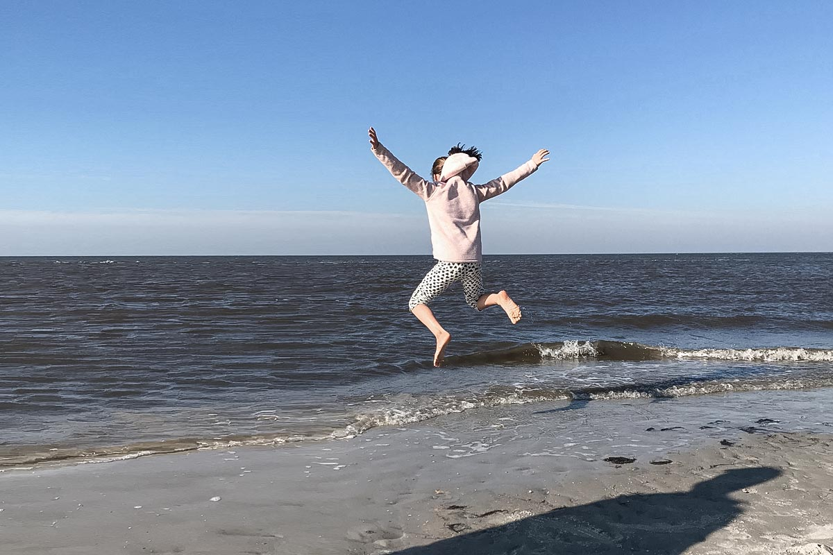 Kinder springt am Meer