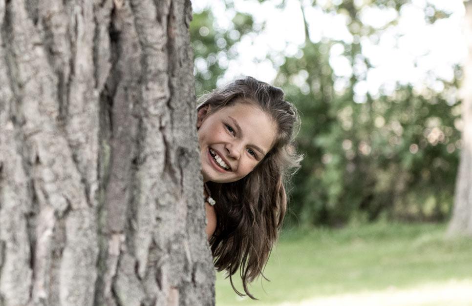 Kind schaut hinter dem Baum hervor